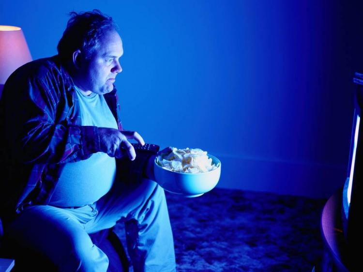 big man eating while watching television